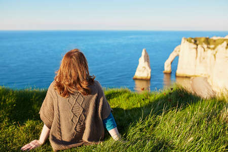 auburn hair: Girl in Etretat, sitting on top of hill and looking at the sea cliffs with arches Stock Photo