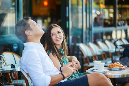 Young romantic couple drinking coffee, eating traditional French croissants and smoking in a cozy outdoor cafe in Paris, France Archivio Fotografico