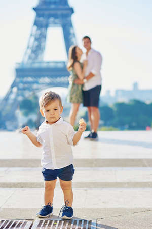 trocadero: Adorable little boy making his first steps in Paris near the Eiffel tower, parents are hugging in the background