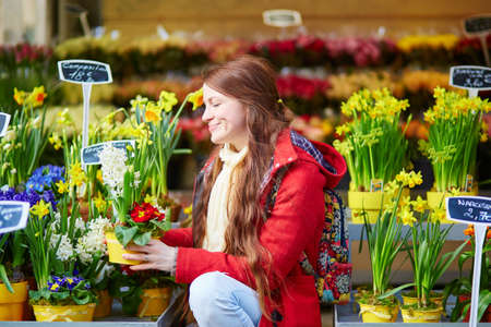 selecting: Beautiful young woman with long hair selecting fresh flowers at Parisian market