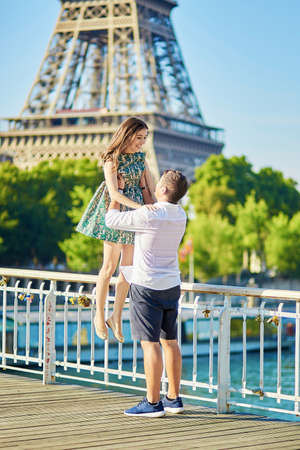 flying kiss: Young romantic couple spending their vacation in Paris, France. Dating couple posing near the Eiffel tower Stock Photo