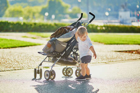 stroller: Cute little boy pushing his stroller in park Stock Photo