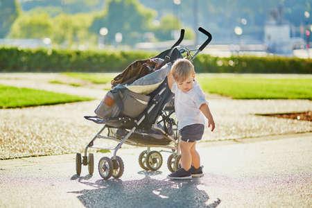 Cute little boy pushing his stroller in park Standard-Bild