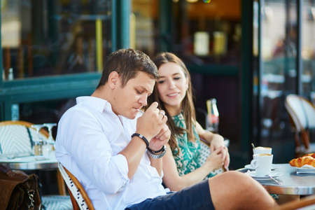Young romantic couple drinking coffee, eating traditional French croissants and smoking in a cozy outdoor cafe in Paris, France Stok Fotoğraf