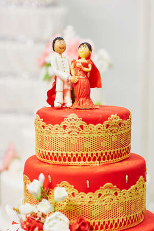 feier: Schöne rote und gelbe Hochzeitstorte im indischen Stil mit Braut und Bräutigam-Figuren auf der Oberseite
