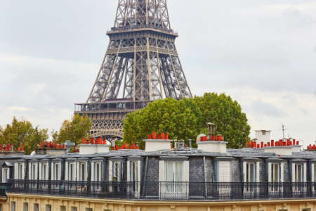 attics: Scenic view of the Eiffel tower over the Parisian roofs with attics and chimneys, Paris, France