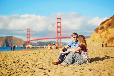 personas sentadas: Rom�ntica pareja amorosa con una fecha en la playa de Baker en San Francisco, California, EE.UU.. Puente Golden Gate en el fondo