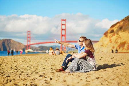 Romantic loving couple having a date on Baker beach in San Francisco, California, USA. Golden gate bridge in the background