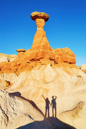 hoodoo: Traveling couple making funny picture of their shadow under the giant hoodoo rock formation in Arizona, USA Stock Photo