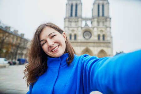 young female: Beautiful young tourist in Paris on a fall day, making funny selfie with Notre-Dame cathedral Stock Photo