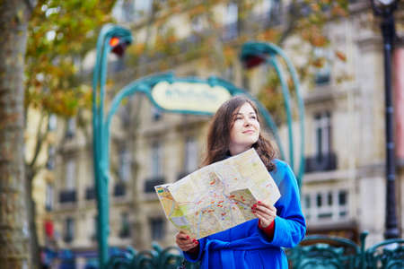 itinerary: Beautiful young tourist in Paris on a fall day, using map and planning her itinerary