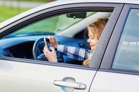 reckless: Young woman using her smartphone while driving a car