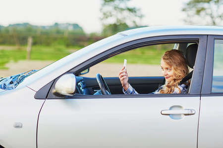 reckless: Young woman using her smartphone and making selfie while driving a car