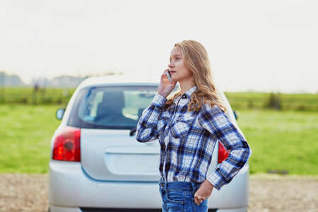 calling for help: Young woman on the road near a broken car calling for help