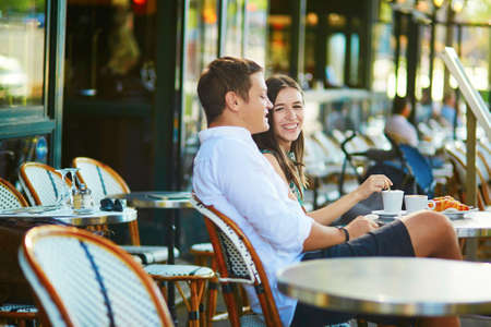 outdoors: Young romantic couple drinking coffee and eating traditional French croissants in a cozy outdoor cafe in Paris, France
