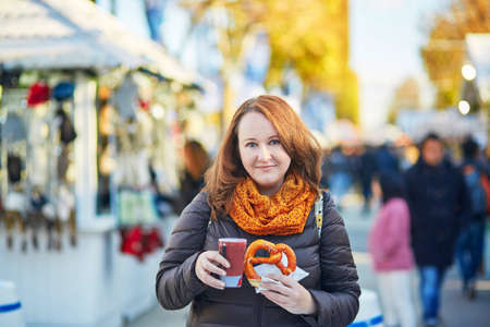 france: Cheerful girl with pretzel and hot wine on Christmas market in Paris, France