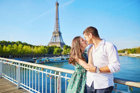 couple dating: Young romantic couple spending their vacation in Paris, France. Dating couple posing near the Eiffel tower Stock Photo
