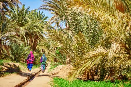 desierto del sahara: Dos mujeres bereberes en ropa nacional caminando en oasis de Merzouga pueblo en el desierto del Sahara, Marruecos