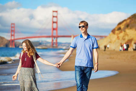 frisco: Romantic loving couple having a date on Baker beach in San Francisco, California, USA. Golden gate bridge in the background