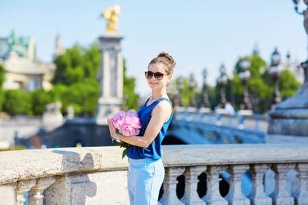 alexandre: Beautiful young Parisian woman in blue blouse with bunch of pink peonies on the Alexandre III bridge in Paris Stock Photo