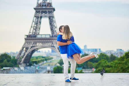 Romantisch daterend paar op Trocadero gezichtspunt in Parijs, is de mens rond te draaien zijn vriendin omhelsde, Eiffel toren is op de achtergrond
