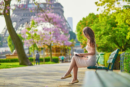 Beautiful young woman in Paris, near the Eiffel tower on a nice and sunny spring day, reading on the bench outdoors Stockfoto