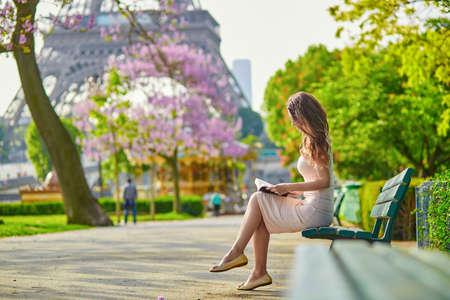 Mooie jonge vrouw in Parijs, nabij de Eiffeltoren op een mooie en zonnige lentedag, lezen op de bank in openlucht Stockfoto