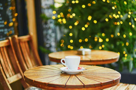 Delicious coffee or hot chocolate in Parisian street cafe decorated for Christmas Standard-Bild