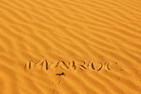 maroc: French word Maroc written on the sand in sand dunes in the Sahara Desert, Merzouga, Morocco Stock Photo