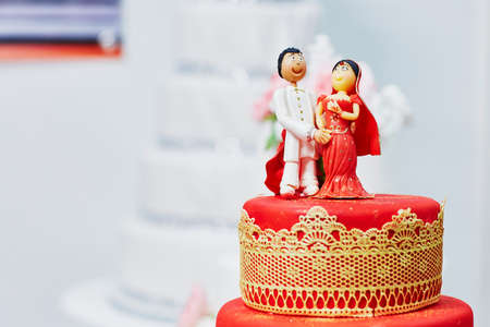 Beautiful red and yellow wedding cake in Indian style with bride and groom figurines on top Reklamní fotografie