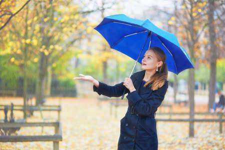 秋や春の雨の日にパリのリュクサンブール庭園の青い傘と美しい若い女性