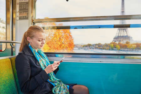 girl sitting: Beautiful young woman travelling in a train of Parisian underground and using her mobile phone. Eiffel tower is behind the window