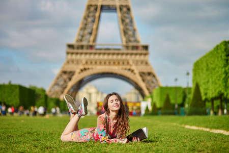 Belle jeune femme à Paris couché sur l'herbe près de la tour Eiffel sur un beau printemps ou en été jour et lire un livre. Étudiant ou écolière faire ses devoirs ou préparer aux examens