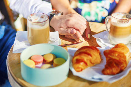 french: traditional French croissants and macaroons in a cozy outdoor cafe in Paris, France Stock Photo