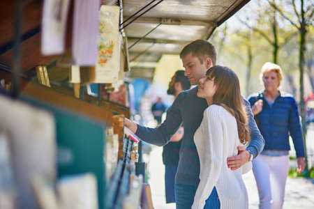 antiquary: Romantic couple in Paris selecting a book from a bookseller near the Seine