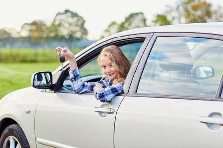 Mooie jonge bestuurder kijkt uit de auto-venster met een sleutel