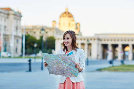 Beautiful young woman walking in Vienna, Austria and using map