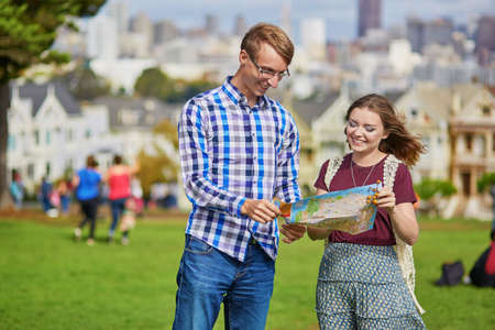 itinerary: Romantic couple of tourists using map and planning their itinerary in San Francisco, California, USA