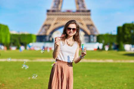 Bella giovane turista o studente ragazza a Parigi soffiando bolle vicino alla Torre Eiffel in una giornata estiva