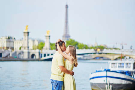 alexandre: Romantic dating couple of tourist in Paris, kissing near the famous Alexandre III bridge over the Seine Stock Photo