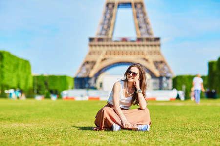 Bella giovane turista o studente ragazza a Parigi che si siede sull'erba vicino alla Torre Eiffel in una giornata estiva Archivio Fotografico