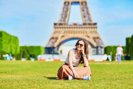 Bella giovane turista o studente ragazza a Parigi che si siede sull'erba vicino alla Torre Eiffel in una giornata estiva Archivio Fotografico - 52440351