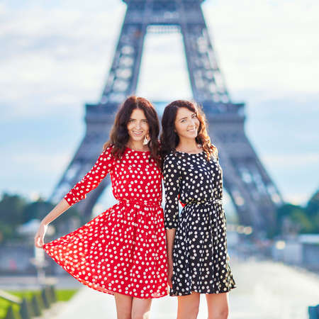 girl in red dress: Beautiful twin sisters in red and black polka dot dresses in front of the Eiffel tower in Paris, France