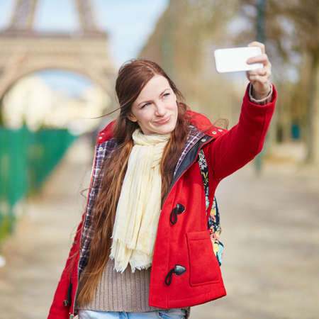 europe travel: Beautiful young tourist in Paris taking selfie using her mobile phone near the Eiffel tower
