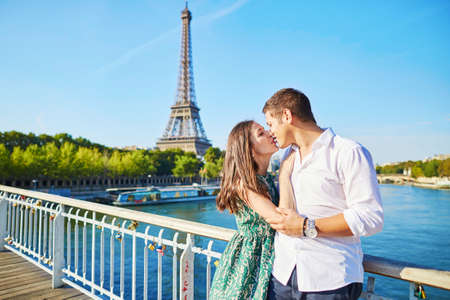 french kiss: Young romantic couple spending their vacation in Paris, France. Dating couple posing near the Eiffel tower Stock Photo