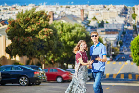 itinerary: Romantic couple of tourists using tablet and planning their itinerary in San Francisco, California, USA Stock Photo