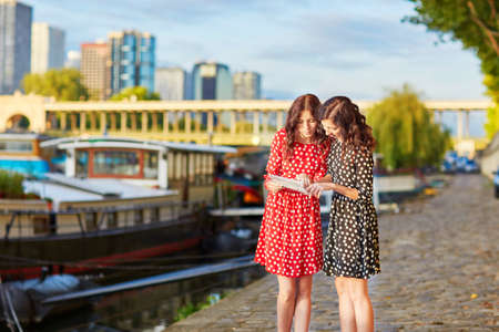 itinerary: Beautiful twin sisters in red and black polka dot dresses near the river Seine in Paris, France, using map