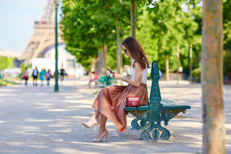 Beautiful young Parisian woman in long skirt near the Eiffel tower on a summer day, sitting on the bench and using mobile phone Stock Photo