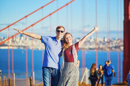 frisco: Romantic loving couple having a date in San Francisco, California, USA. Golden gate bridge in the background