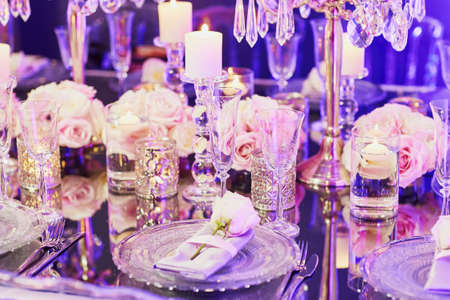 Elegant table set for an event party or wedding reception, in purple light